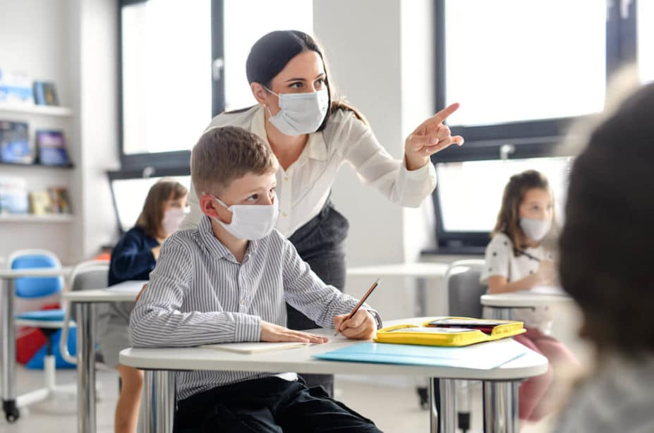 Image of teacher and student wearing PPE when in school classroom.