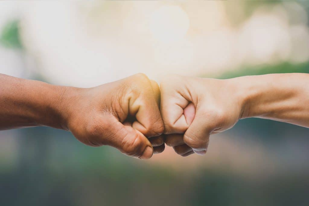 Image of two people fist bumping
