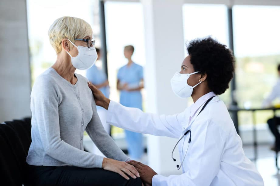 Image of doctor and patient wearing PPE in hospital.
